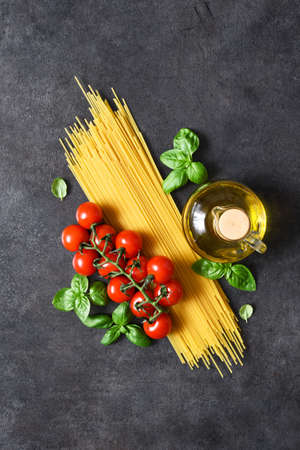 Spaghetti, tomatoes and basil on a black concrete background. Ingredients for pasta with text space. Layout.