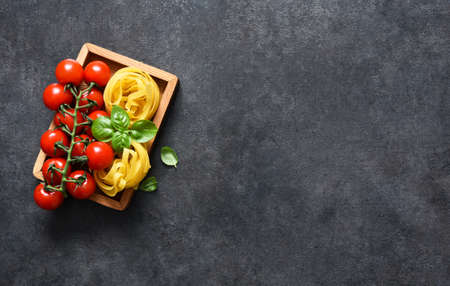 Ingredients for the pasta. Tagliatelle pasta, tomatoes and basil on a black concrete background.