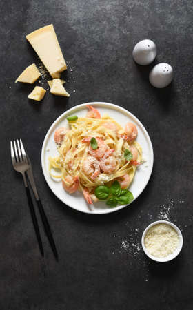 Tagliatelle pasta with creamy sauce, parmesan and shrimps in a plate on a black background. View from above. 스톡 콘텐츠
