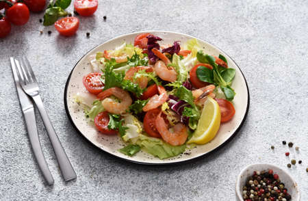 Mix salad with tomatoes and grilled shrimps with sauce and clematis on the kitchen table. Concrete food background. 스톡 콘텐츠