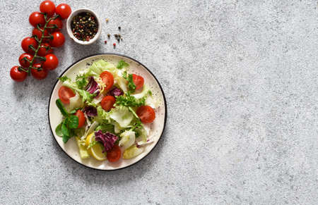 Green mix salad with vegetables and sauce on a concrete background.