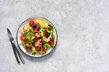 Mix salad with tomatoes and grilled shrimps with sauce and clematis on the kitchen table. View from above. Concrete food background.