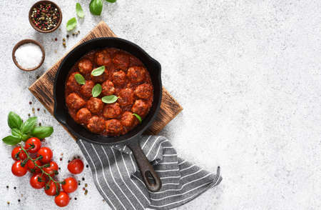 Meat balls with tomato sauce in a frying pan on a light concrete background.