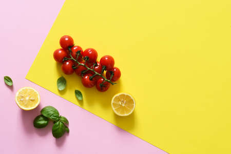 Lemon slice and bunch of cherry tomatoes on a yellow, pink background. Food trend concept.