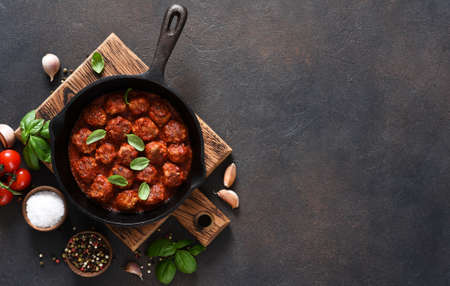 Meat balls with tomato sauce with garlic and basil in a frying pan on a brown background.