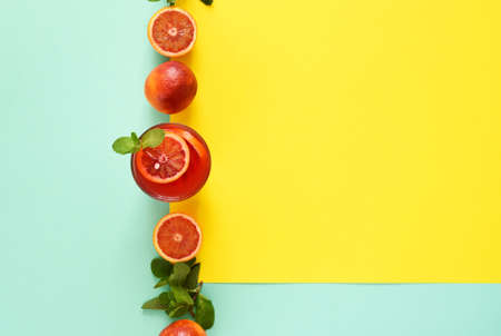 Red orange juice with mint on a blue, yellow background. Summer minimalist concept 2021. Pop art design, creative summer concept. Standard-Bild