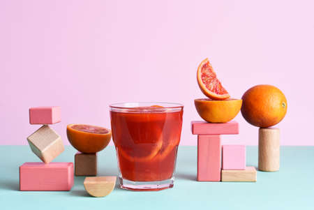 Red orange juice in a glass with geometric shapes. Pop trend 2021. The concept of beautiful food.