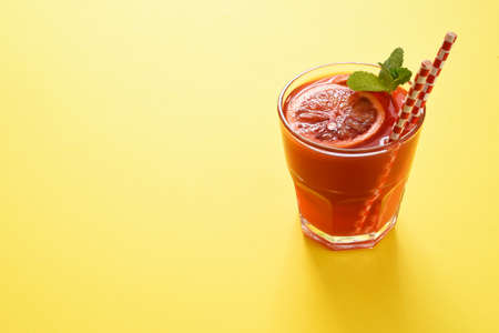 Red orange juice in a glass on a yellow background. Beautiful food concept, trend 2021.