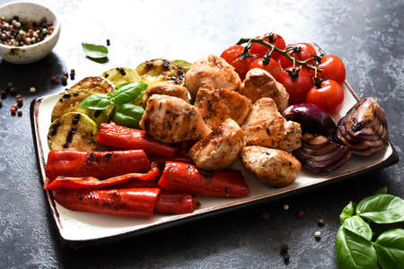 Grilled meat and vegetables set: tomatoes, onions, zucchini, peppers in a plate on a concrete background. Picnic. BBQ menu.