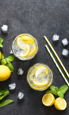 Cold lemonade with mint and ice on a black concrete background, top view. Stock fotó