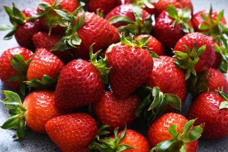 Beautiful fresh strawberries in a plate on a concrete background.