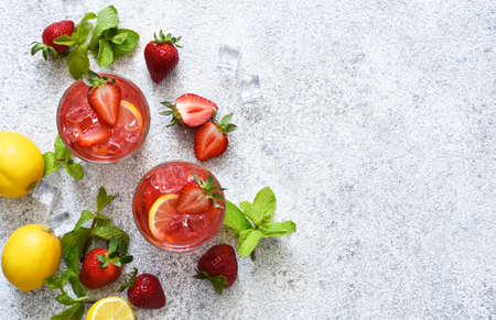 Strawberry lemonade with ice and mint, top view. Cold drink with strawberries.