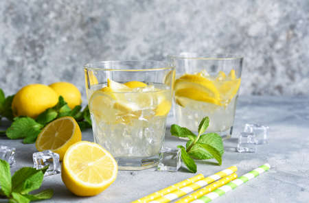 Cold lemonade with lemon, mint and ice on a concrete background. Stock fotó