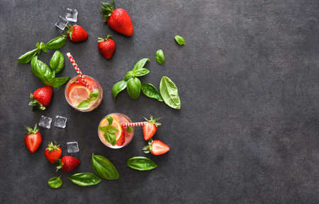 Summer drink. Cold lemonade with strawberries and basil on a concrete background. Stock fotó