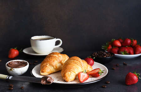 Croissant with chocolate paste and a cup of coffee, strawberries on the kitchen table. Traditional snack or breakfast.