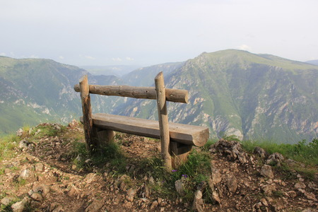 chasm: Lonely wooden bench on the edge of a high precipice overlooking the deep abyss