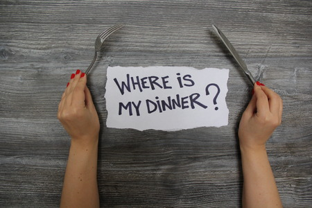 textural: Where is my dinner? Fork in the left hand and knife in the right hand on the gray wooden textural background Stock Photo