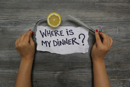 Where is my dinner? Fork with lemon in the left hand and knife in the right hand on the gray wooden textural background Banco de Imagens
