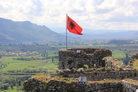 Red Albanian flag with a double-headed black eagle waving in the wind over the top of old stone fortress Rozafa