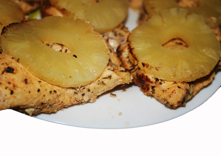 Tasty baked chicken cooked with ripe pineapple. Фото со стока