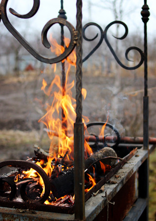 combustion: Beautifully burning dry firewood in wrought grill. Stock Photo