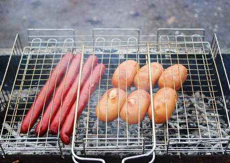 Very tasty grilled sausages on a grill in the smoke. Stock Photo