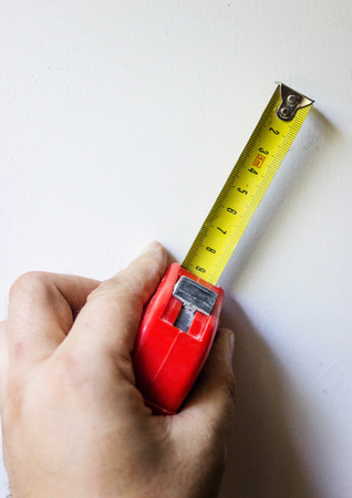 Yellow roulette for measuring the length in the mans hand