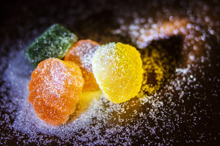 Multicolored marmalade in sugar on a dark background.