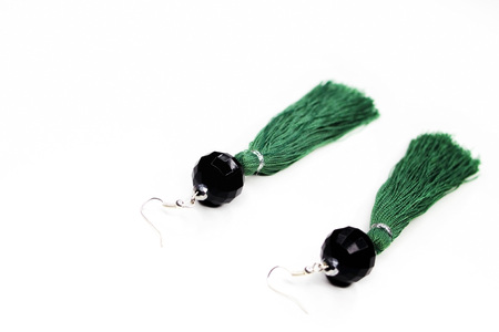 Beautiful hanging earrings of green color on a white background