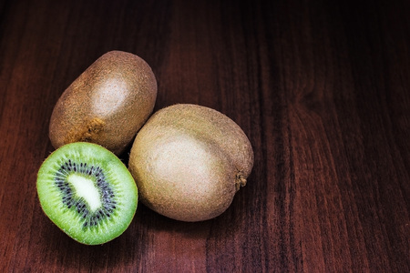 Kiwi close-up on a mahogany background. Isolate.