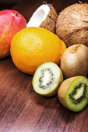 Fresh juicy citrus fruits in a basket on a wooden background Stock Photo