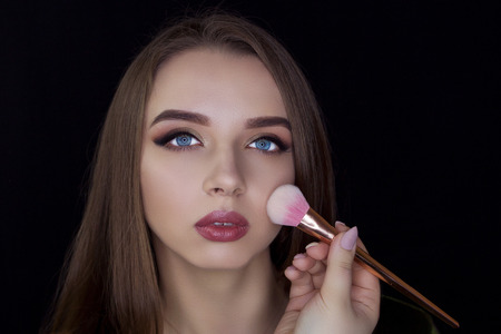 A girl on a black background holds a make-up brush. Professional makeup. We do make-up.