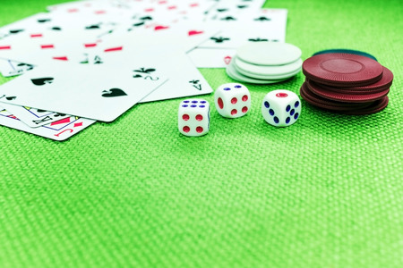 Casino equipment placed on the green floor for risky gambling for the people who want to get rich. Stock Photo