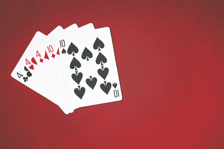 Cards for Poker on a red background, full house.