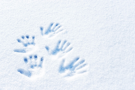 Handprints in the snow. Symbol of friendship in the snow. Different palms on the snow. Archivio Fotografico