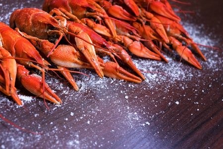 Red crayfish on a wooden background with seasonings. Imagens