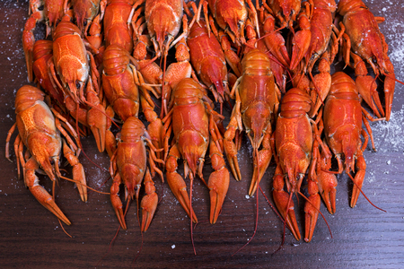 Crayfish with salt on a dark wooden table.