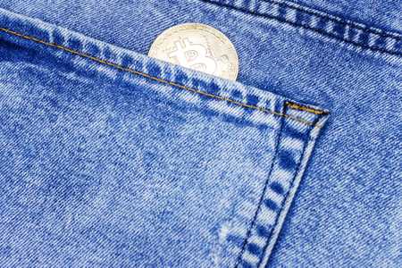 Bitcoin in your pocket. Money in your pocket. Gold bitcoin coin on jeans. Bitcoin jeans pocket. Stock Photo