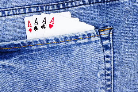 Playing cards, aces in jeans pocket close up.