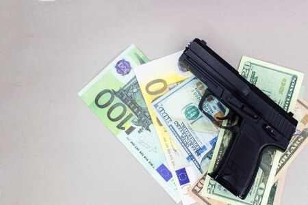 Gun and money on a gray background