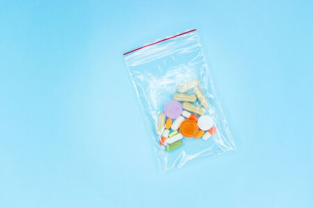 Pills in a plastic bag on a blue background Stok Fotoğraf