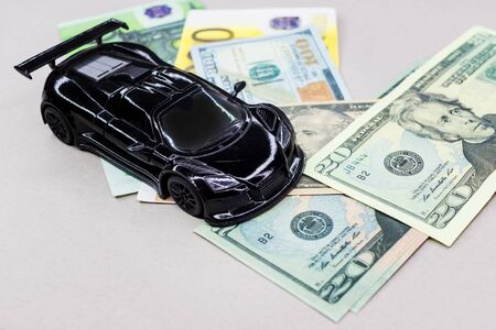 Miniature car model and Financial statement with coins. Finance and car loan, saving money for a car or material design concepts.