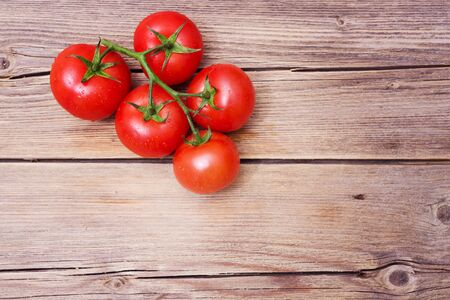 Tomatoes on a wooden background, a branch of tomatoes on the table.