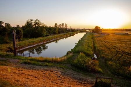 Irrigation river during the sunset in the wheat fields of Emilia Romagna. Castelnovo di Sotto - Italy Archivio Fotografico