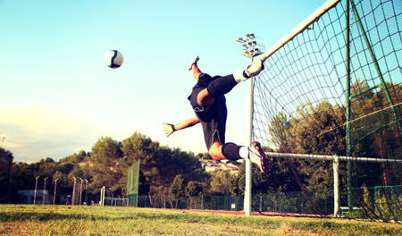 diving save: Goalkeeper diving to stop the soccer ball Stock Photo
