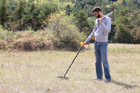 metal detector: Man using a metal detector on lawn.