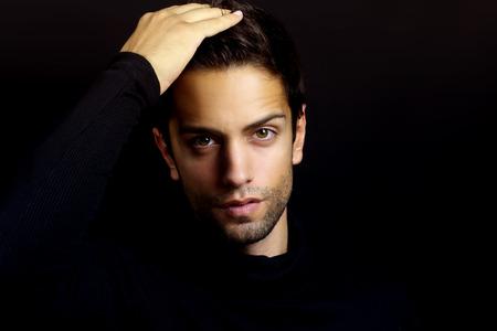 modelos hombres: retrato de una bella morena con un cuello alto sobre un fondo negro