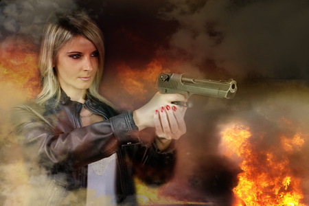 sexy woman holding up her weapon with explosion behind her Reklamní fotografie