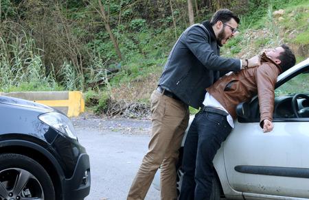 a man strikes a man after having had an accident Standard-Bild
