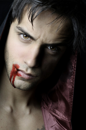 evil man: portrait of a handsome vampire with blood flowing from the mouth